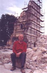 Milko Kelemen in front of the ruins of the Catholic church in Vocin destroyed during Greater Serbian agression on Croatia in 1991 (photo from www.viroviticko-podravska-zupanija.hr)